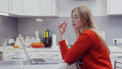 Beautiful young blonde talks with friends by videocall sitting at the kitchen Footage