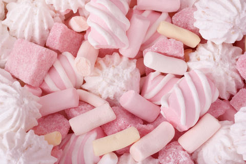 Sweet junk food pink background with marshmallow and fruit lump sugar Photo