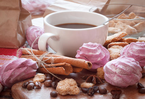 Cup of coffee with sweet food and condiments Photo