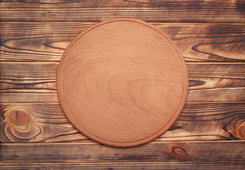 Round wooden plate on wooden table フォト