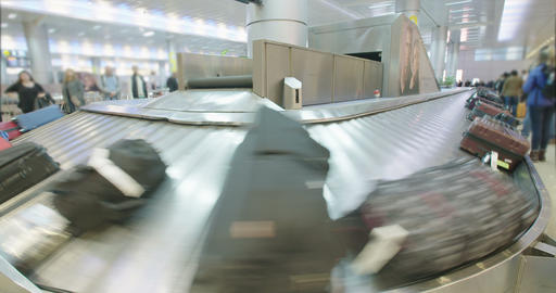 Passengers collecting luggage from a conveyor belt at the airport Footage