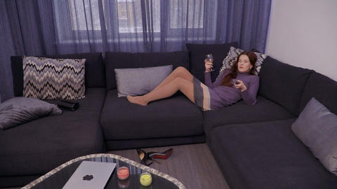 Attractive girl drinks wine and watches tv relaxing at home after work day Footage