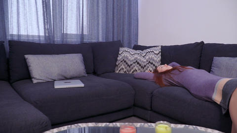Young woman in casual dress lays on sofa and stretches herself Footage