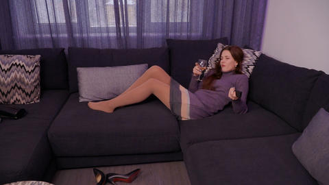 Pretty young brunette watches tv and drinks wine at home Footage