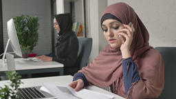 Young beautiful girl in pink hijab working with documents and talking on mobile Footage
