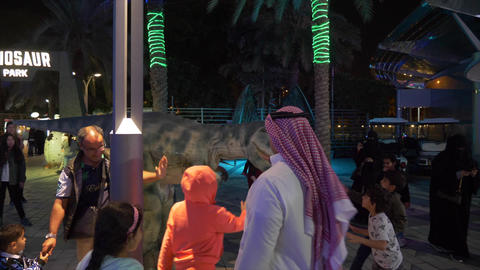 Dubai, UAE - January 13, 2018: Arabian man touch dinosaurus. Happy children Live Action