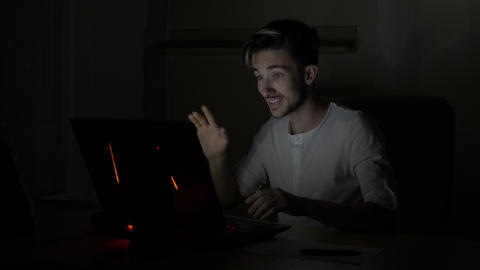 Young attractive student male video chatting and waving at web camera in a dark Footage