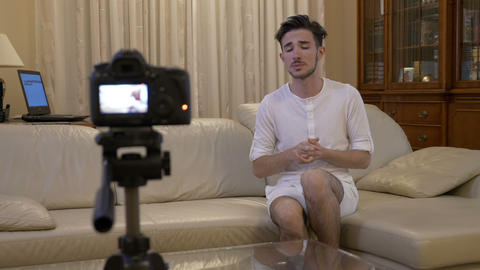 Male vlogger recording a video tutorial at home on couch about online business Footage