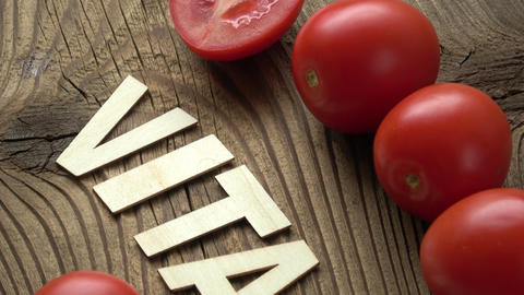Tomato with inscription VITAMIN on brown wooden surface background Live Action