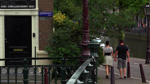 Couple Walking Through Canal Area In Amsterdam At Leidsegracht stock footage