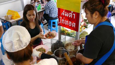 Girl Ordering som tam, Isan food at Lalai Sap Market in Silom Bangkok Footage