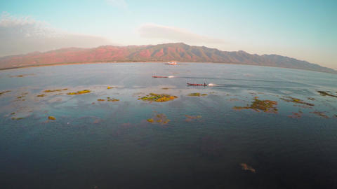 Flying over boats on Inle Lake at sunset 4k Footage