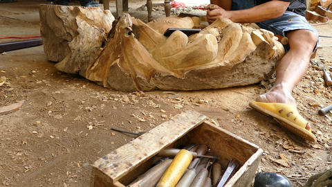 Wood carving tools while a guy is working on a carving Footage