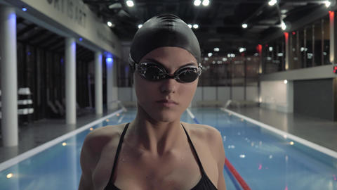 Woman swimmer in goggles making stretching exercise for swimming in water pool Footage