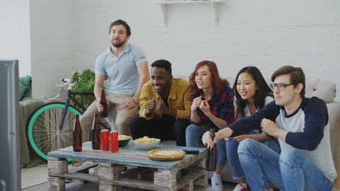 Multi ethnic group of friends sports fans watching sport event on TV together Live Action
