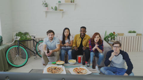 Group of young friends watching olympic games match on TV together eating snacks Footage