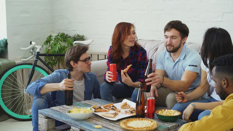 Happy friends have party talking and eating pizza. They clink bottles sitting on Footage