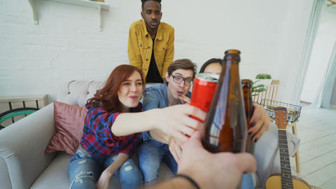 POV shot of male hand clinking beer bottle with friends while celebrating party Footage