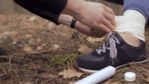Man wraps a woman's damaged ankle with bandage Footage