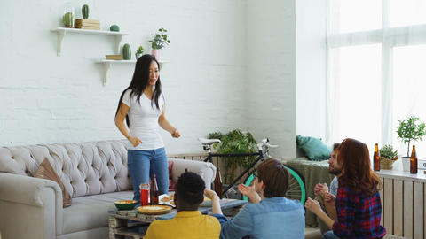 Young asian girl playing party game with her multi ethnic friends at home Footage