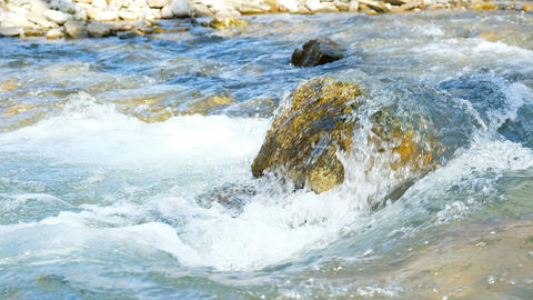 Mountain stream, water is washed by a large stone on a sunny day, 4k Footage