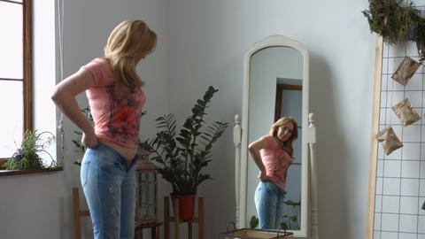 Woman struggling trying to fit into tight jeans Footage