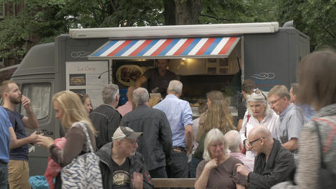 Gourmet food truck during local gathering with people waiting to buy tasty meals Footage
