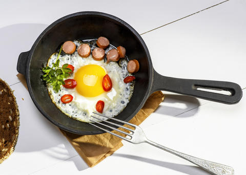 fried egg with pieces of sausage in a round black cast-iron fryi Photo