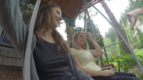 Pretty teen female friends swinging on a swing in backyard relaxing and having Footage