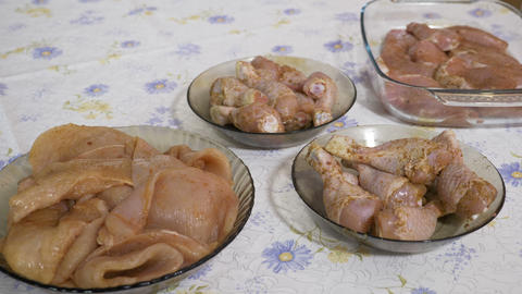 Raw seasoned meat chicken breast arranged in dishes on a table by woman Footage