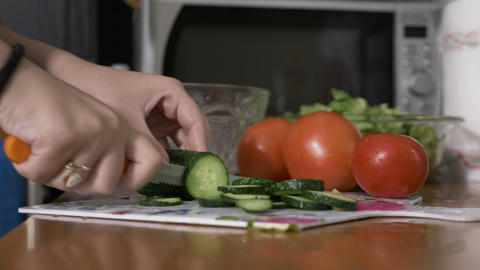 Vegan women hand slicing cucumber preparing a fresh salad with healthy Footage