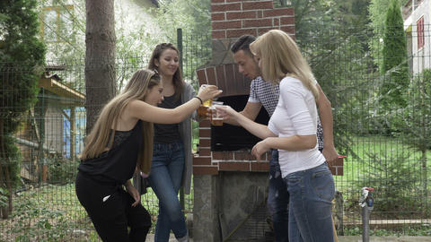 Millennials friends raising beer glasses for a toast having fun at the outdoor Footage
