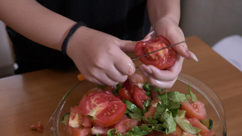 Hands of raw vegan woman slicing tomatoes for season salad healthy diet concept Footage
