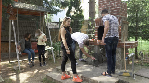 Millennials boys and girls friends gathered together in backyard preparing grill Footage