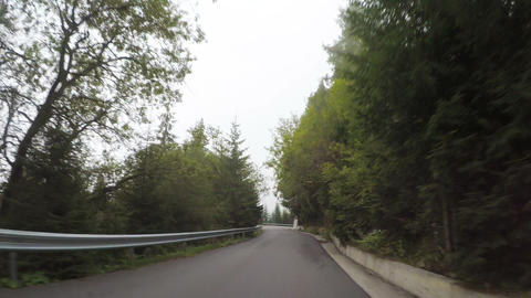 POV of picturesque mountain landscape seen from automobile driving on zig zag Footage