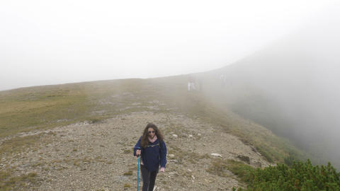 Hiker teenage woman walking to explore mountains attractions on path with fog Footage