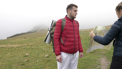 Young lost funny tourists couple on adventure trip in mountain studying together Footage