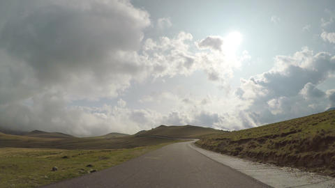 Pov of countryside road with hills and cloudy sky in background seen from drive Footage