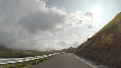 Fast timelapse POV of driving car on curving route with hills and cloudy sky on Footage