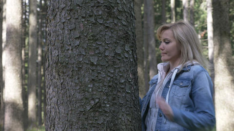Sensitive beautiful woman caressing and embracing a tree in the wood forest Live Action