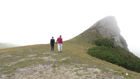 Back view of young couple holding their hands enjoying their walk on mountain Footage
