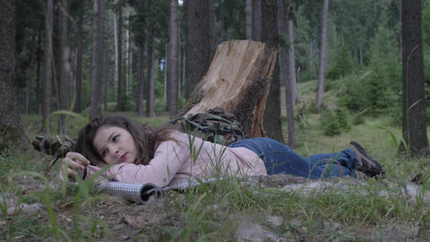 Attractive young woman resting down the grass in the woods enjoying silence and Footage