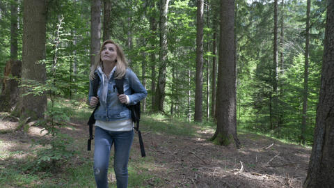 Relaxed female traveler hiking alone in a beautiful refreshing forest wearing Live Action
