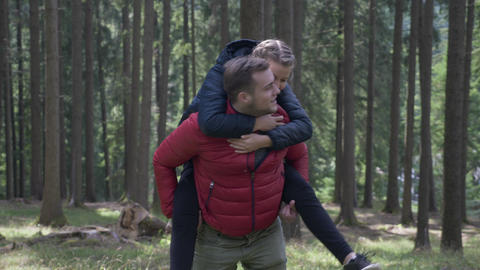 Young man giving his girlfriend a piggy back ride having fun in their hike in Footage