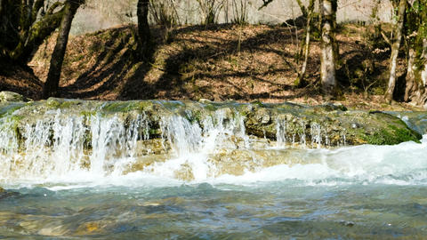 A mountain stream runs in a spring forest, a small waterfall, 4k Live Action