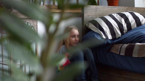 Sad little girl hugs doll sitting anxiety at corner Footage