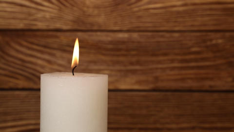 Close up white candle trembling flame over wood Footage