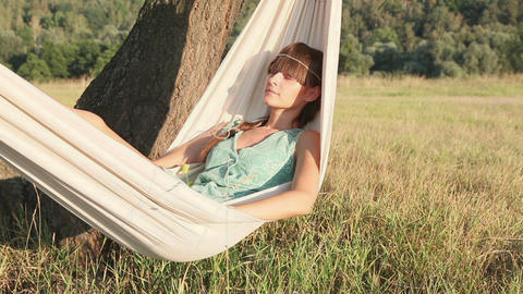 Pretty Young Girl Swinging On Hammock At Sunset stock footage