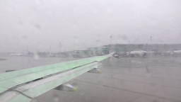 Aircraft taxiing to runway, green defroster dispersed on wing, cold weather Footage
