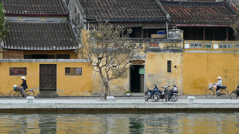Vietnamese ladies on a bicycle passing by at the river front in the old town Footage